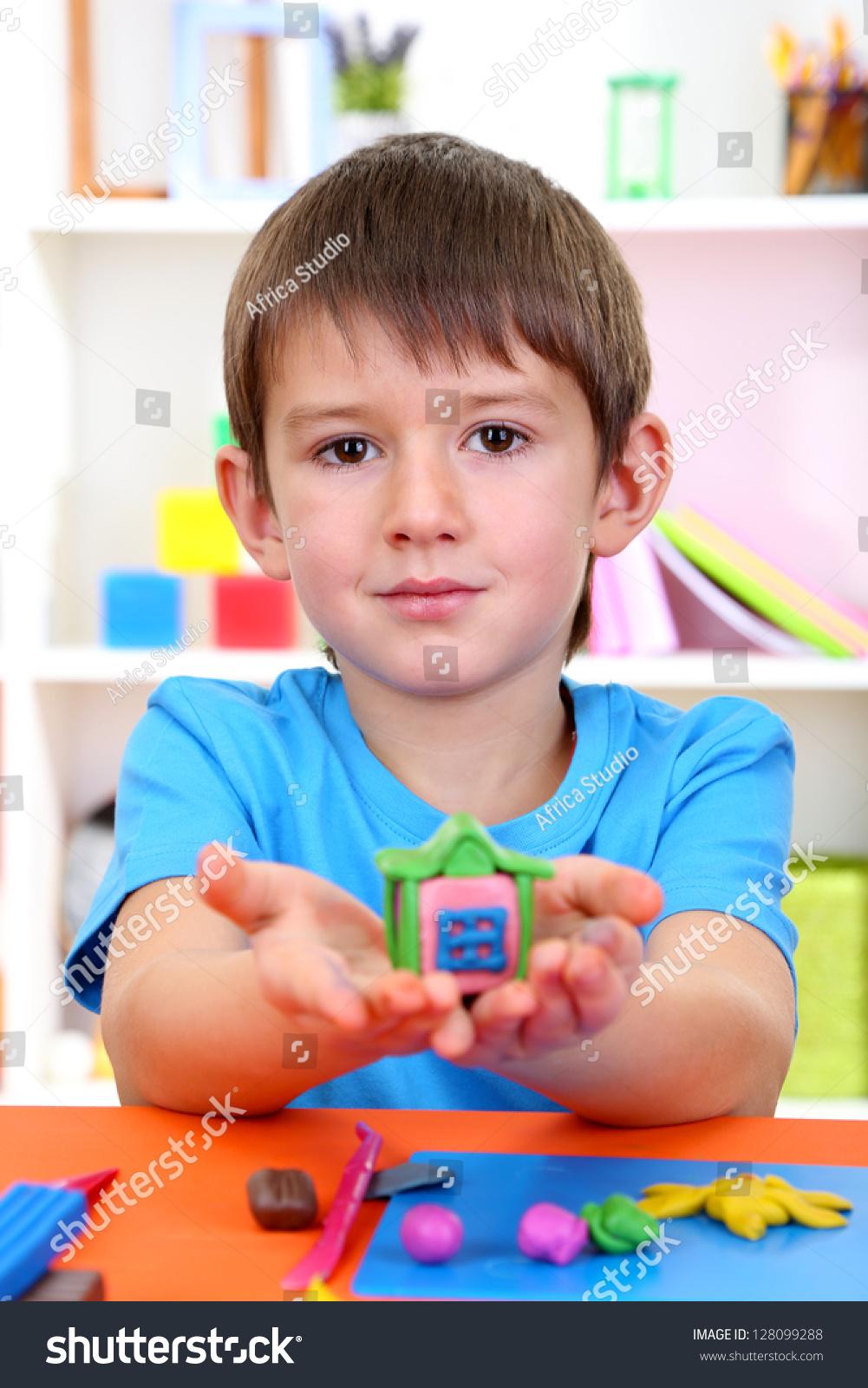 可爱的小男孩抱着手工制作的橡皮泥房子在桌上-人物