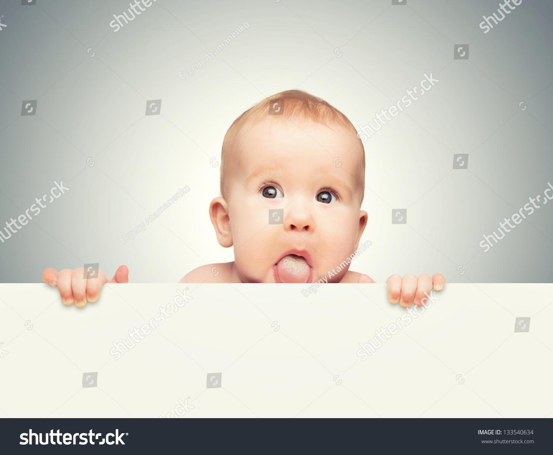 有趣可爱的宝宝手里拿着白色空白旗帜孤立在一个灰色
