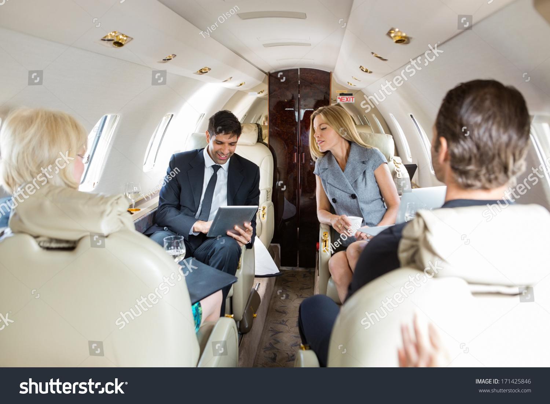 商人在私人飞机使用数字平板电脑与同事