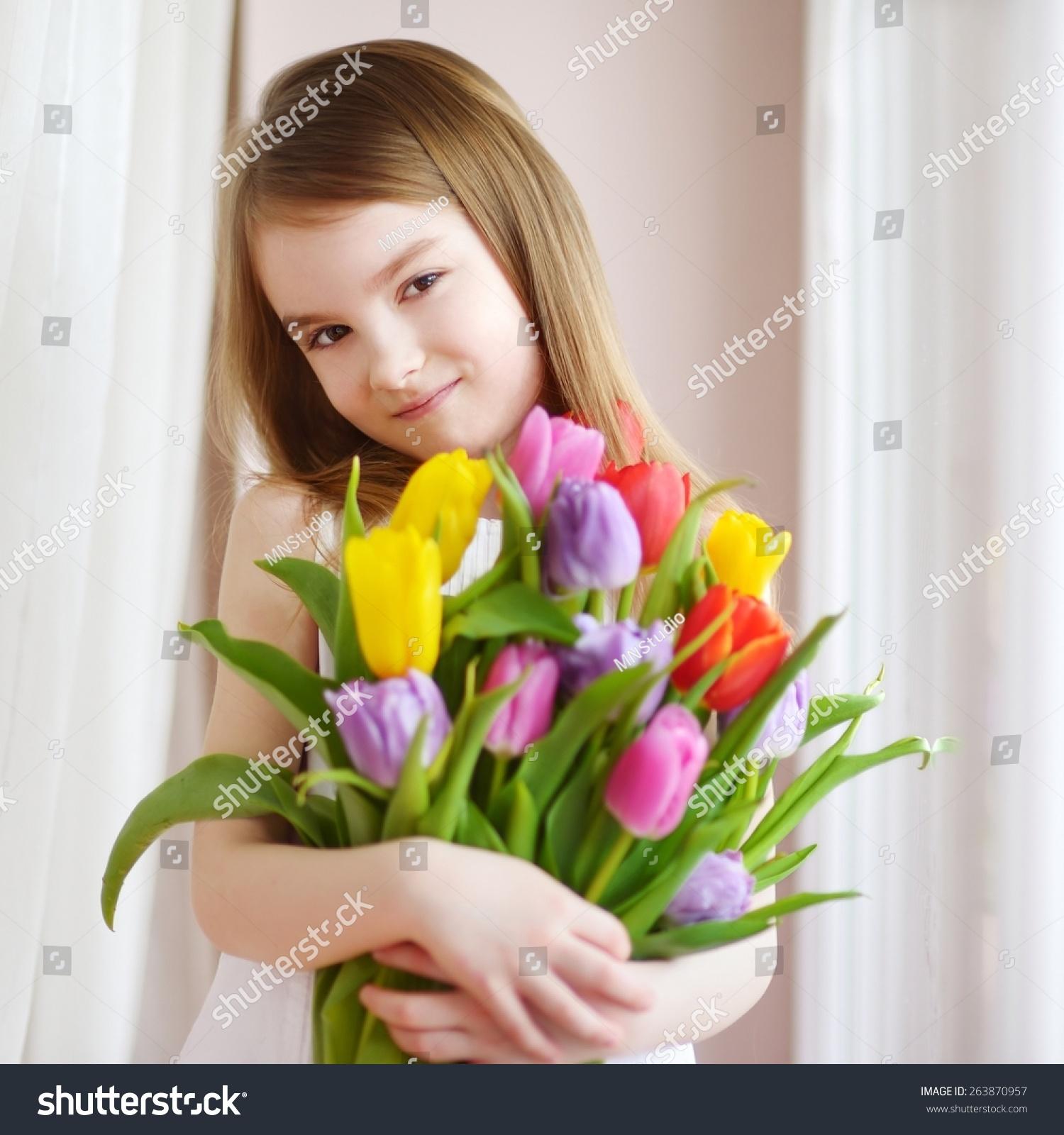 可爱的小女孩拿着郁金香的窗口-人物