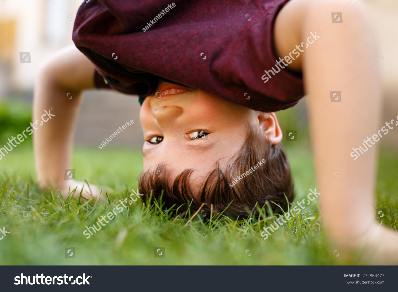小男孩头手倒立在草地和笑