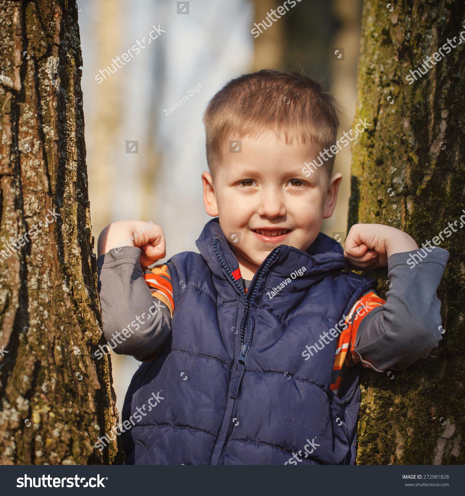可爱的小男孩站在树在阳光明媚的春天-人物