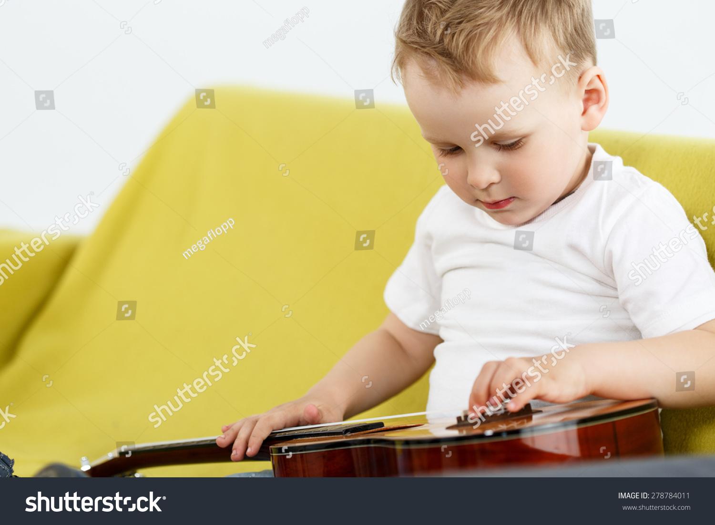 小孩坐在沙发上,检查尤克里里琴吉他