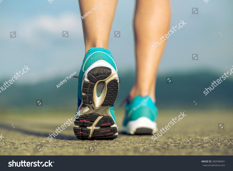 阳光下跑步运动员的脚上运行的道路.-人物,运动/娱乐