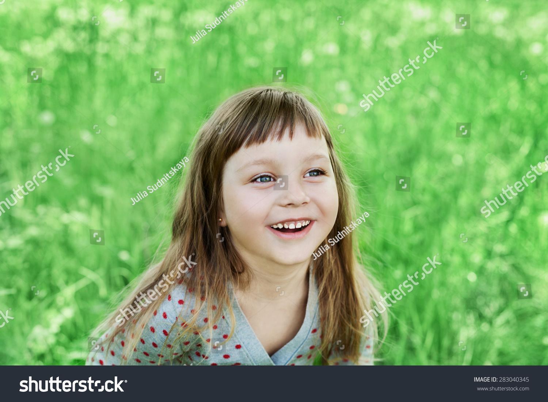 可爱的小女孩在绿色的草地上室外的笑,快乐的童年概念