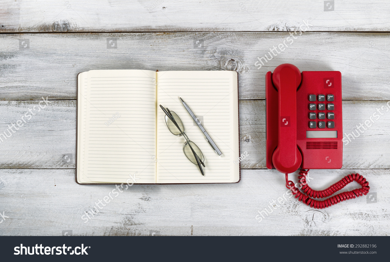red wayfarer glasses  red phone, notepad, pen
