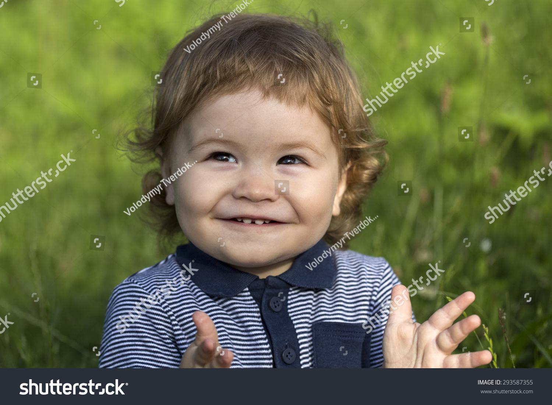 小可爱快乐的小男孩与金发卷曲的头发微笑和坐在新鲜