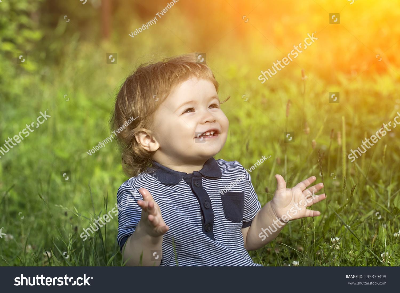 小可爱的快乐微笑的男孩坐在鲜绿的草地上晴天,水平的