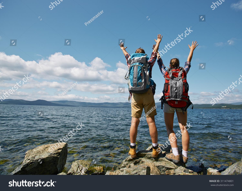 两个旅行者与提高武器在海边享受暑假-人物,运动/娱乐
