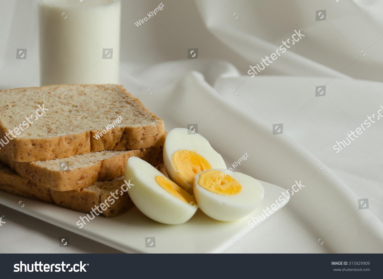 简单的早餐,煮鸡蛋,全麦面包和一杯牛奶