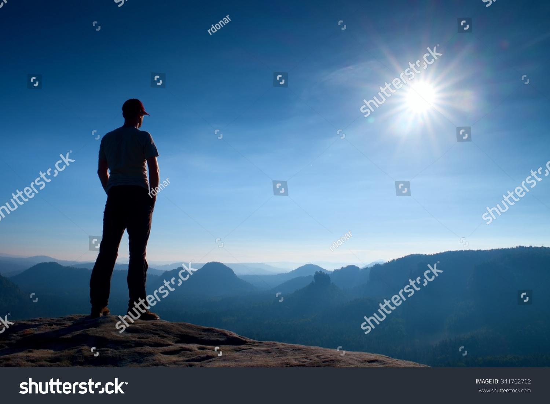 独自徒步旅行者在红色帽子站在砂岩岩石的峰岩帝国公园和看雾,雾蒙蒙
