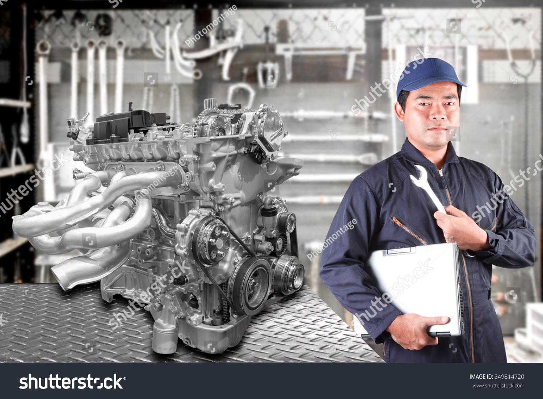 汽车维修拿着电脑和工具在发动机修理汽车修理店